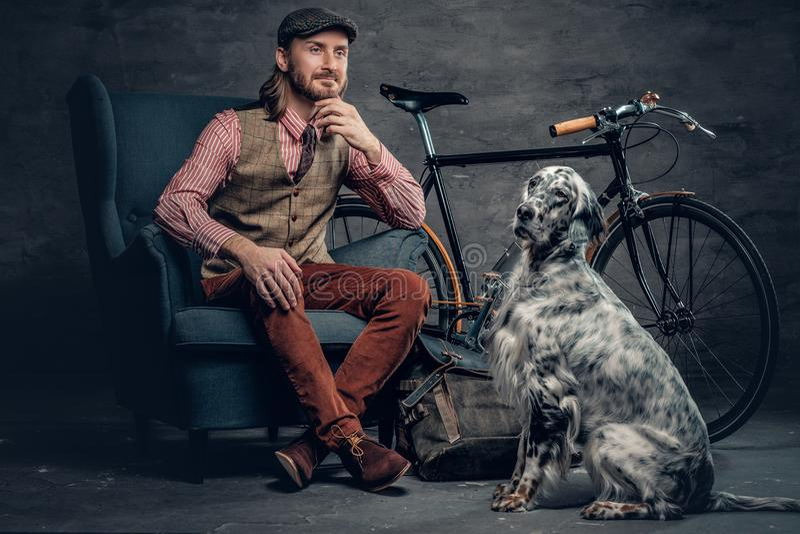 Stilfull man med långt hår som poserar med den Irland setter och singl fotografering för bildbyråer