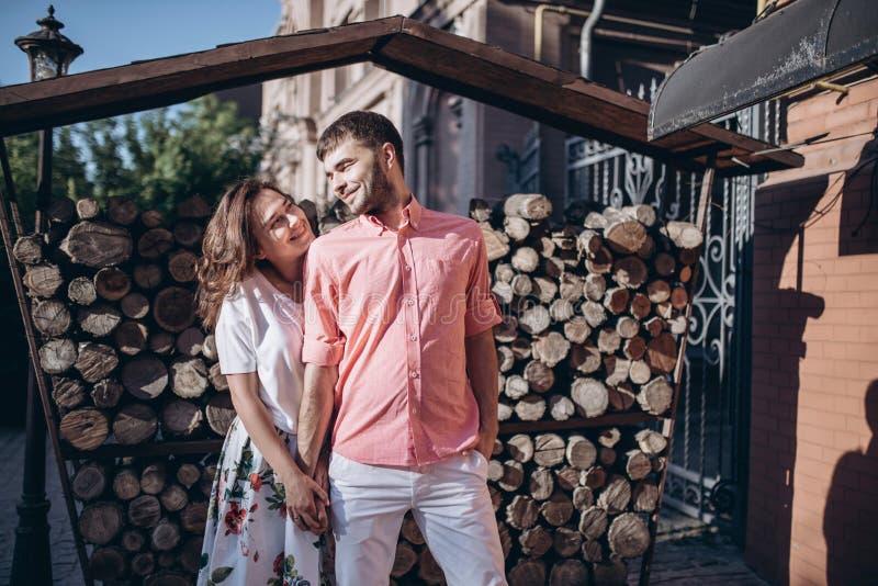 Stilfull man och lycklig kvinnaomfamning i ljus på bakgrund av trävedträväggen Lyckliga par hagging, det romantiska ögonblicket arkivbilder