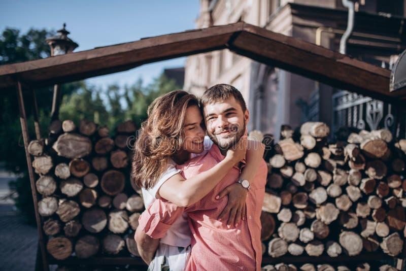 Stilfull man och lycklig kvinnaomfamning i ljus på bakgrund av trävedträväggen Lyckliga par hagging, det romantiska ögonblicket arkivbild