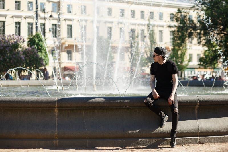 Stilfull man på springbrunnen i varm sommardag Honom som bär i svart jeans, svart T-tröja, svart lock med riundsolglasögon royaltyfria foton