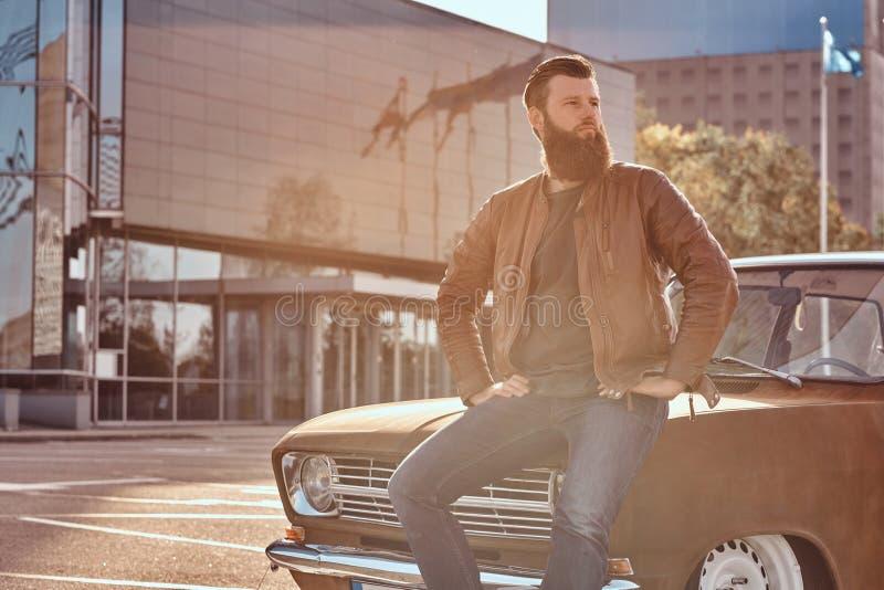 Stilfull man som lutar på den stämda retro bilen i staden som parkerar nära skyskrapa på den ljusa solnedgången royaltyfria foton