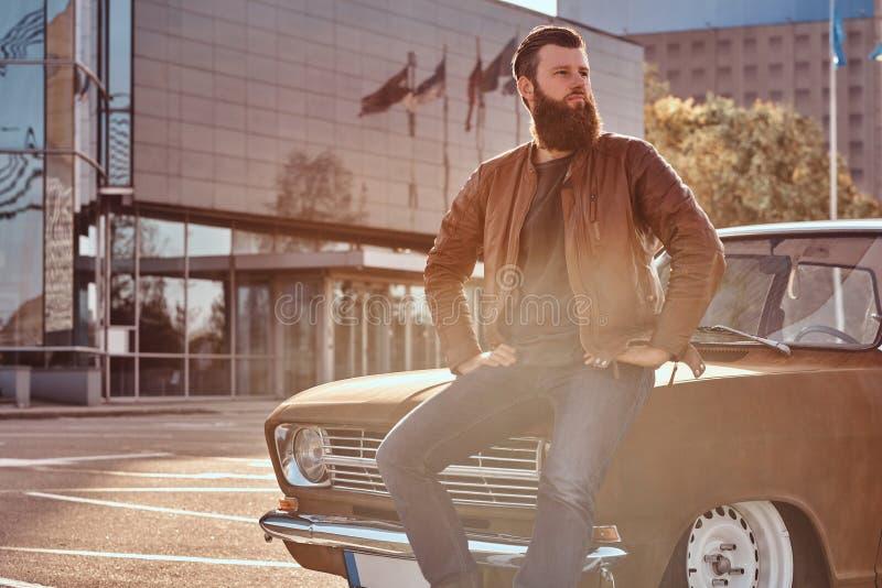 Stilfull man som lutar på den stämda retro bilen i staden som parkerar nära skyskrapa på den ljusa solnedgången arkivfoton