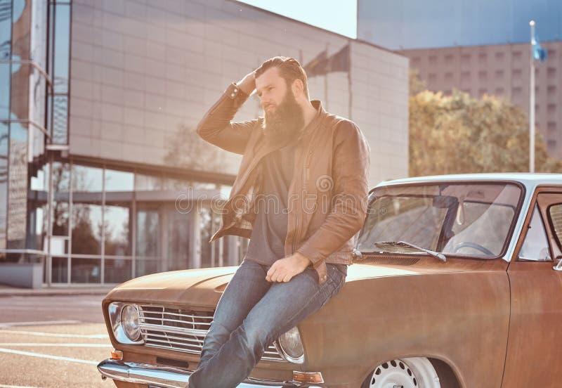 Stilfull man som lutar på den stämda retro bilen i staden som parkerar nära skyskrapa på den ljusa solnedgången fotografering för bildbyråer