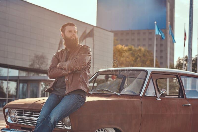 Stilfull man som lutar på den stämda retro bilen i staden som parkerar nära skyskrapa på den ljusa solnedgången royaltyfri bild