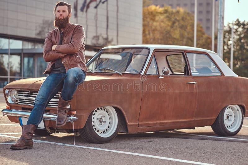 Stilfull man som lutar på den stämda retro bilen i staden som parkerar nära skyskrapa på den ljusa solnedgången arkivbild