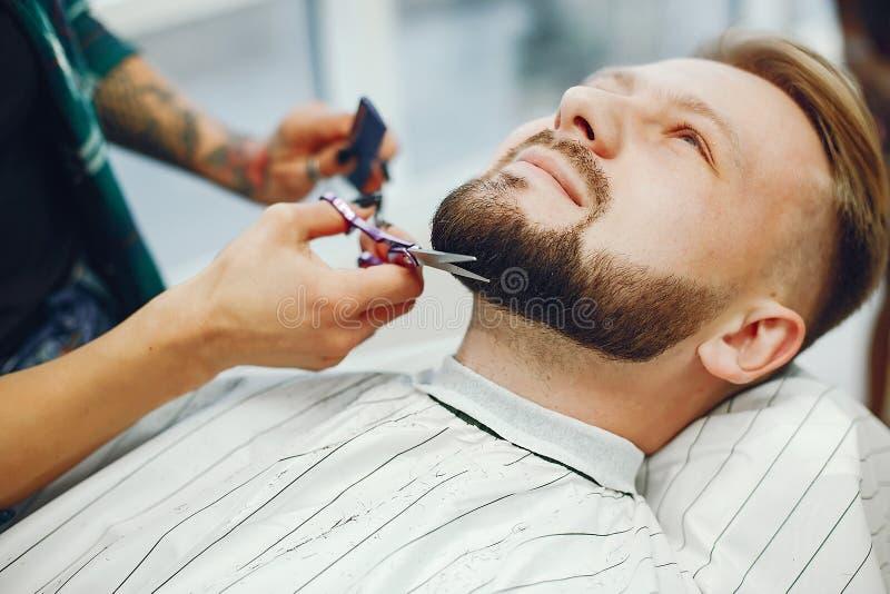 Stilfull man som sitter i en frisersalong fotografering för bildbyråer