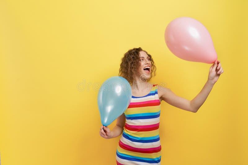 Stilfull modell i den randiga klänningen som rymmer två ballons royaltyfri bild