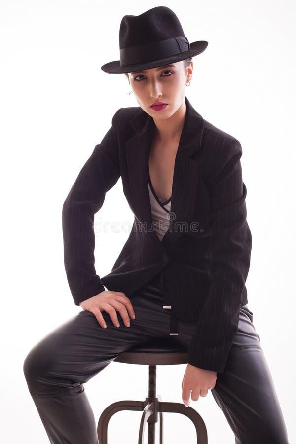Stilfull modemodell som poserar att sitta på en stol som bär en retro hatt över en vit bakgrund i studio arkivbild