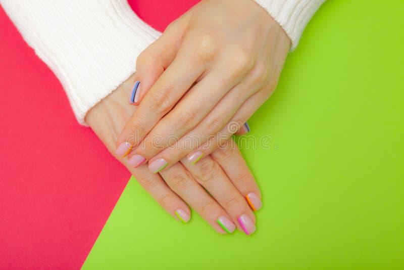 Stilfull moderiktig kvinnlig manikyr Härliga ung kvinnas händer på rosa och grön bakgrund arkivfoto