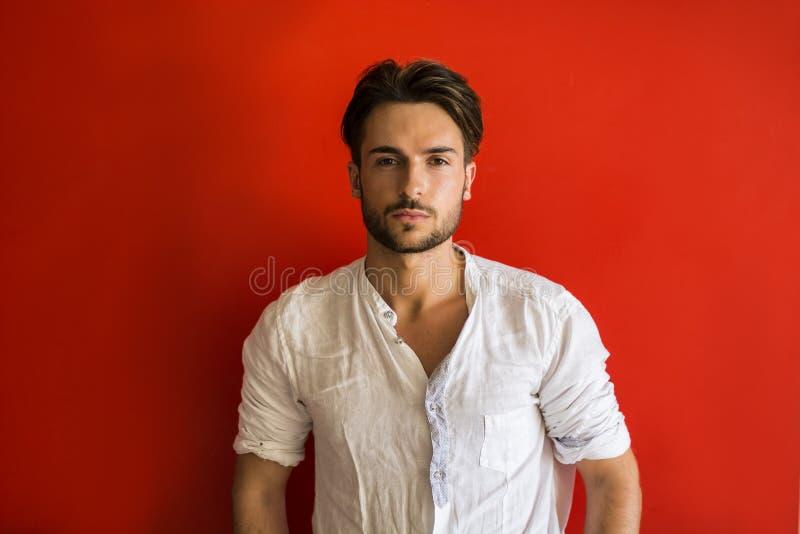 Stilfull moderiktig ung man som står den utomhus- röda väggen royaltyfri bild