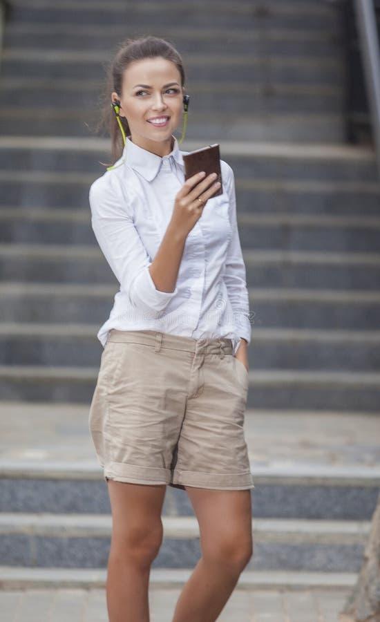 Stilfull modern Caucasian brunettkvinna som utomhus poserar royaltyfria bilder