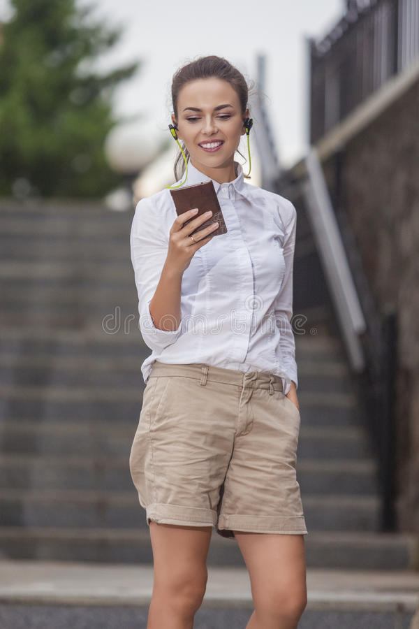 Stilfull modern Caucasian brunettkvinna som utomhus poserar med Smartphone royaltyfri fotografi