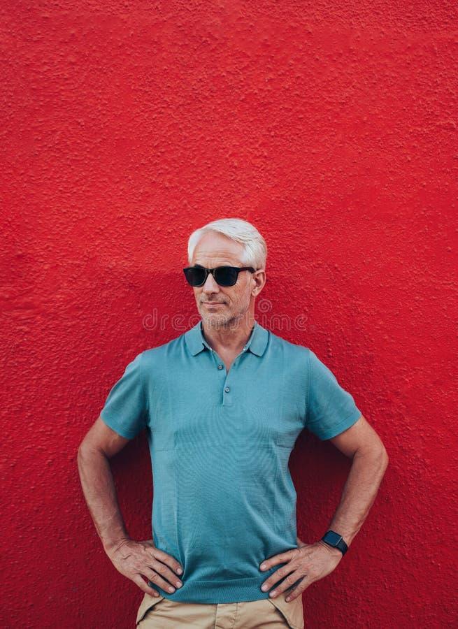 Stilfull mogen man som poserar mot den röda väggen royaltyfri bild