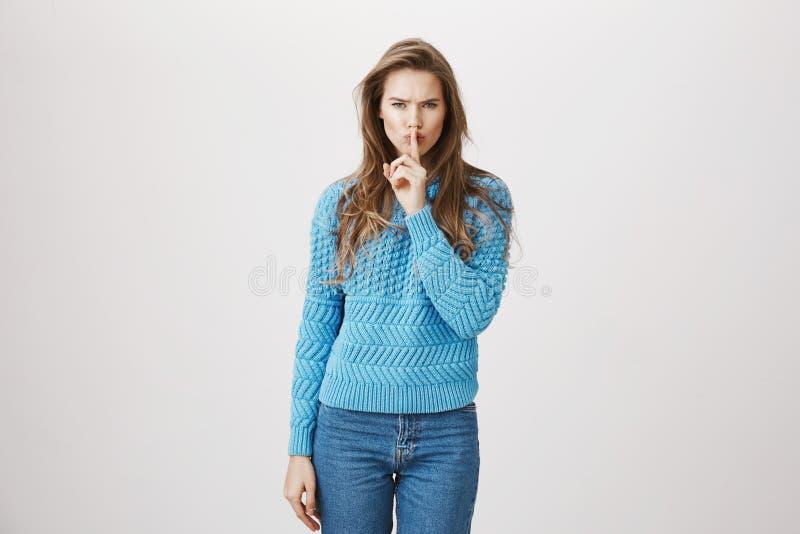 Stilfull och attraktiv europeisk kvinna i den moderiktiga blåa tröjan som uttrycker allvar, medan visa shh underteckna med indexe royaltyfri bild