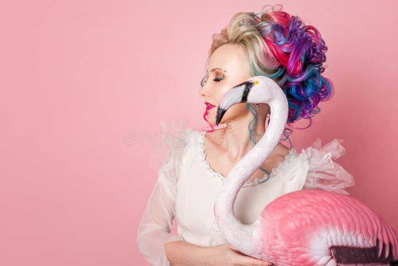 Stilfull och härlig kvinna med kulört hår Krama ett rosa flamingodiagram arkivbilder
