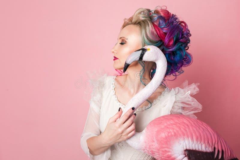 Stilfull och härlig kvinna med kulört hår Krama ett rosa flamingodiagram arkivfoto