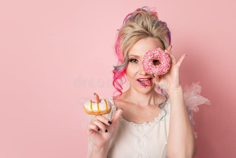 Stilfull och härlig kvinna med kulört hår Två donuts som exponeringsglas, rolig grimas arkivfoto