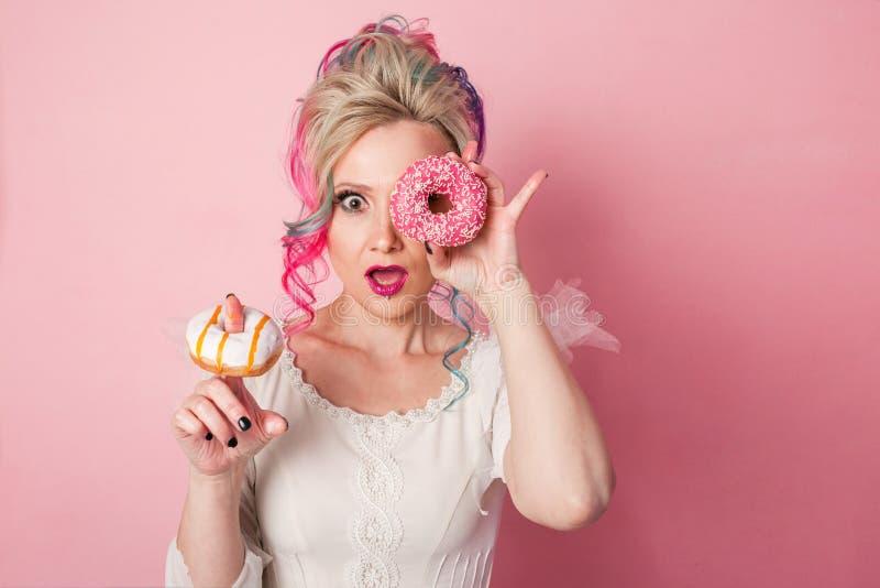 Stilfull och härlig kvinna med kulört hår Två donuts som exponeringsglas, rolig grimas royaltyfri foto