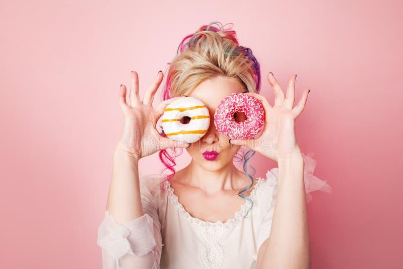 Stilfull och härlig kvinna med kulört hår Två donuts som exponeringsglas, rolig grimas fotografering för bildbyråer