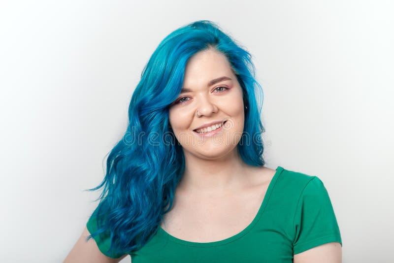 Stilfull och modebegrepp för ungdom, - den unga härliga kvinnan med blått hår ler över vit bakgrund fotografering för bildbyråer