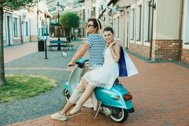 Stilfull parridning på sparkcykel- och innehavshoppingpåsar utomhus royaltyfri foto