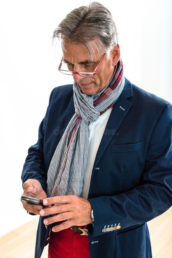 Stilfull pensionär som kontrollerar hans mobiltelefon royaltyfria bilder