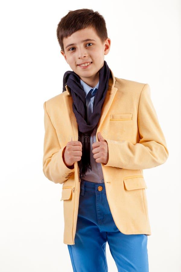 Stilfull pojke i gult omslag och bl?a fl?sanden som isoleras p? vit bakgrund royaltyfria foton