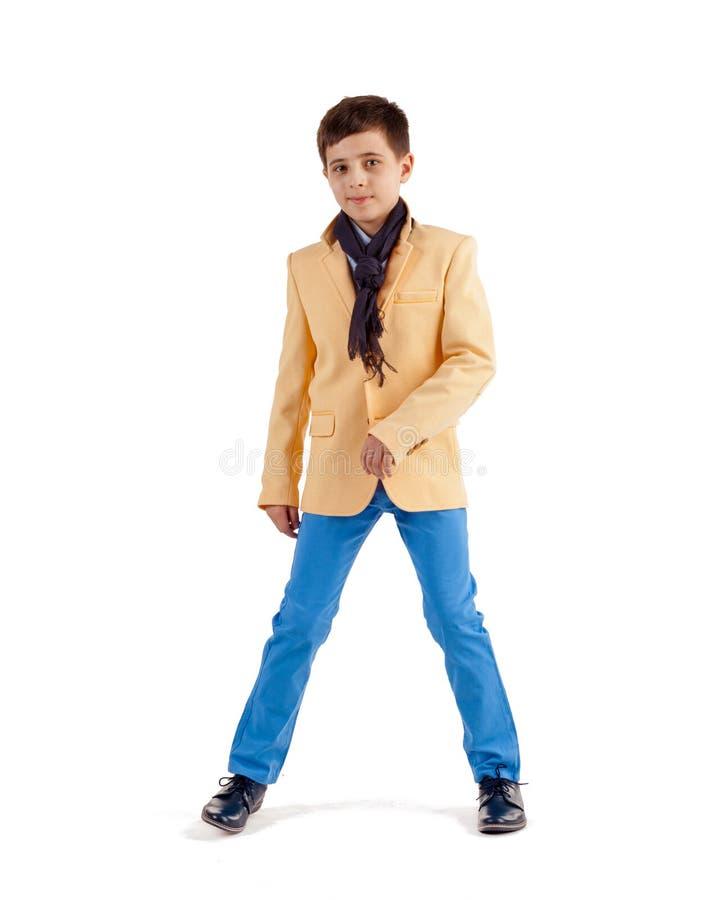 Stilfull pojke i gult omslag och bl?a fl?sanden som isoleras p? vit bakgrund arkivfoto