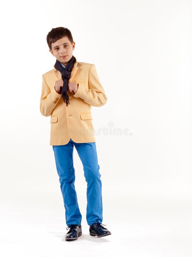 Stilfull pojke i gult omslag och bl?a fl?sanden som isoleras p? vit bakgrund fotografering för bildbyråer