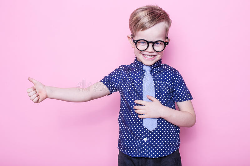 Stilfull pojke i skjorta och exponeringsglas med stort leende skola förträning Mode Studiostående över rosa bakgrund arkivbild