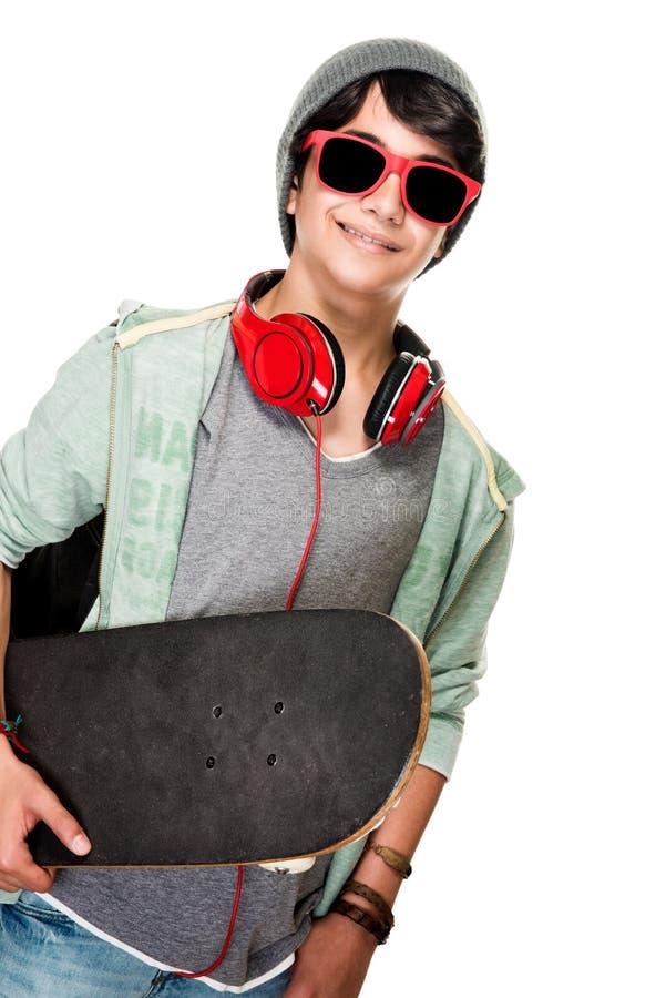 Stilfull pojke med skateboarden royaltyfria foton