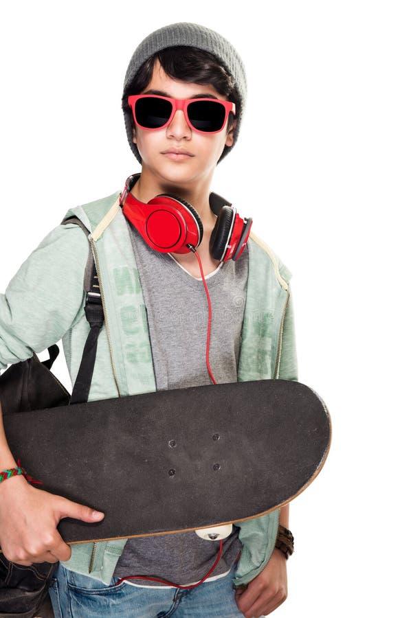 Stilfull pojke med skateboarden royaltyfri bild