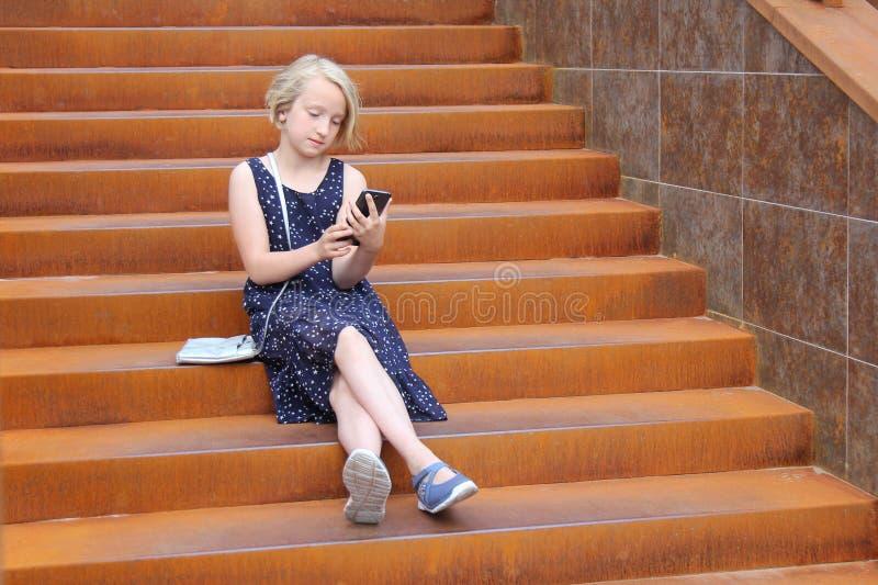 Stilfull preteenflicka som använder ett telefonsammanträde på en rostig trappuppgång Barn- och grejbegrepp arkivbilder