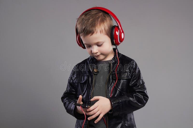 Stilfull pys i hörlurar lyssnande musik för stiligt barn fotografering för bildbyråer