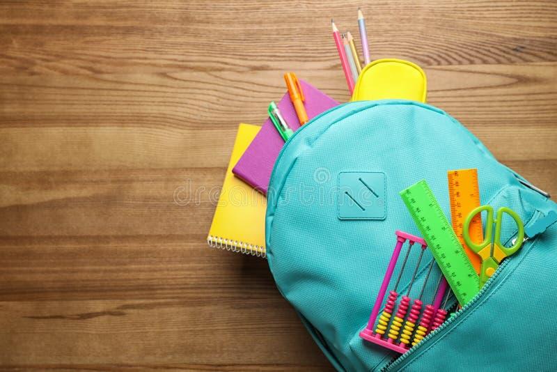 Stilfull ryggsäck med olik skola som är stationär på trätabellen Utrymme f?r text fotografering för bildbyråer