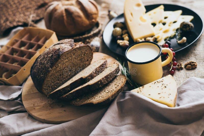 Stilfull sammansättning av organisk mat som är förberedd för frukostägg, ost bröd och örter i en maträtt, på träklipp arkivbild