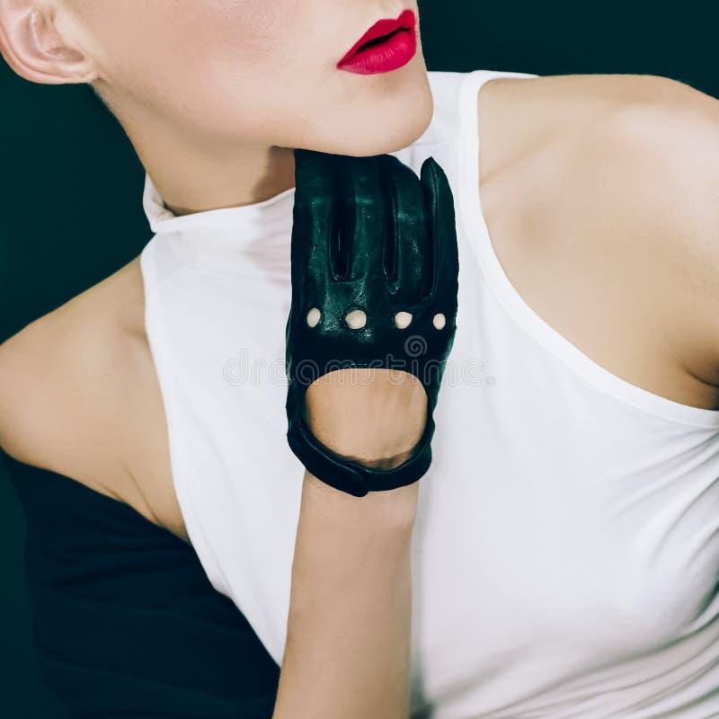 Stilfull sexig modell på svart bakgrund i moderiktiga handskar och Jac royaltyfria foton
