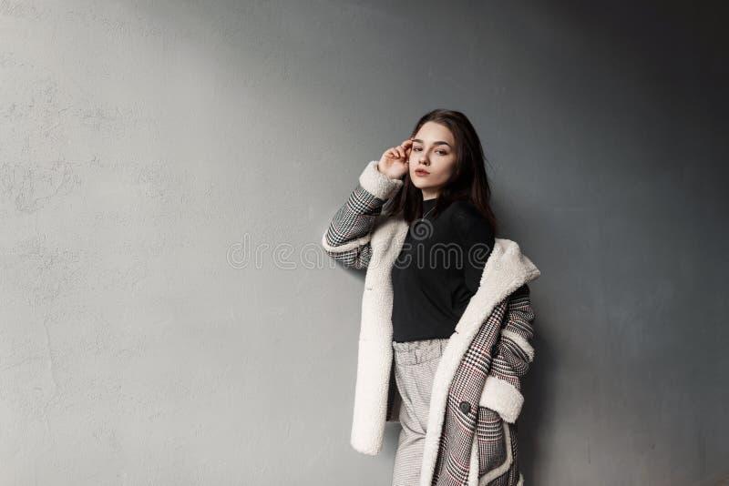 Stilfull sinnlig ung brunettkvinna i en moderiktig skjorta i ett grått rutigt omslag för tappning i trendigt vila för byxa arkivbilder