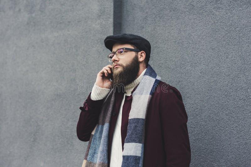 stilfull skäggig man som framme talar vid telefonen av arkivfoto