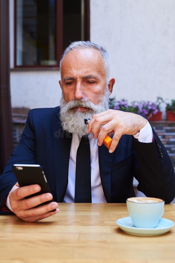 Stilfull skäggig man som ser smartphonen royaltyfri fotografi