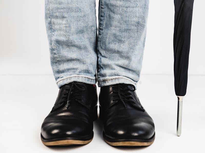 Stilfull sko-, paraply- och man` s lägger benen på ryggen fotografering för bildbyråer