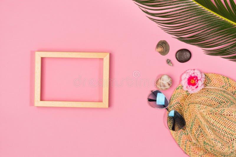 Stilfull sommarsammansättning med fotoramen, gröna sidor, hatten och solglasögon royaltyfri fotografi
