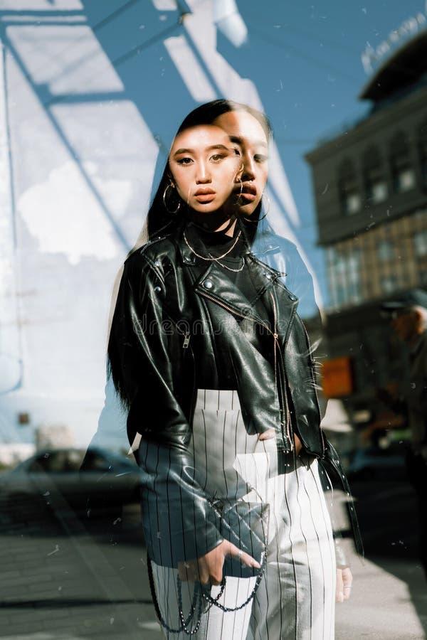 Stilfull stående för gata av en flicka av det asiatiska utseendet på gatorna av staden med dubbel exponering på en solig dag tren royaltyfri fotografi