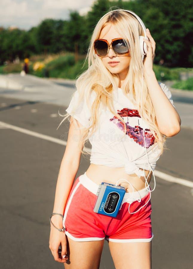 Stilfull stående för utomhus- sommarmode av den unga nätta sexiga blonda flickan som poserar i vinagesolglasögon och lyssnar till royaltyfri fotografi