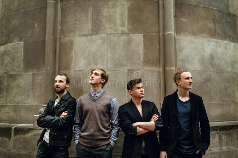 Stilfull stilig grupp av män som står och poserar på backgroen royaltyfri fotografi