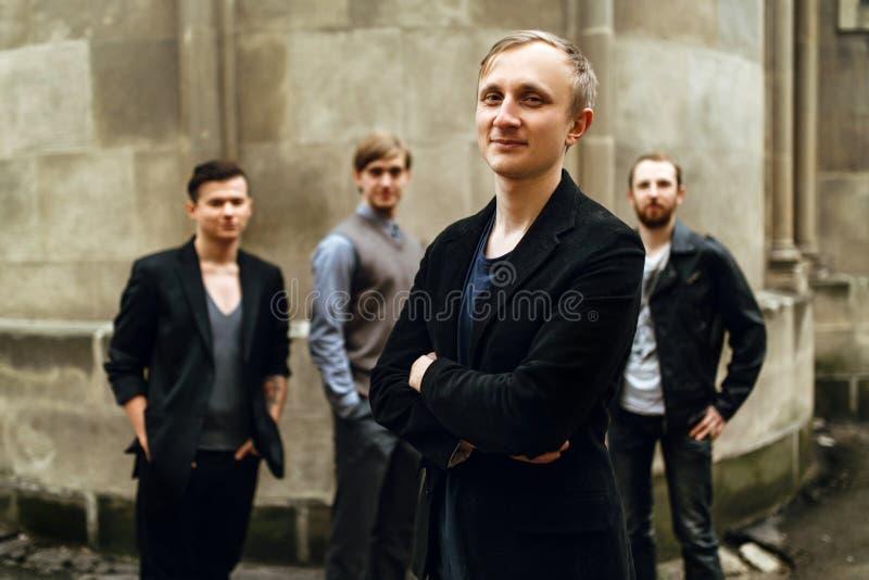 Stilfull stilig grupp av män som står och poserar på backgroen arkivbild