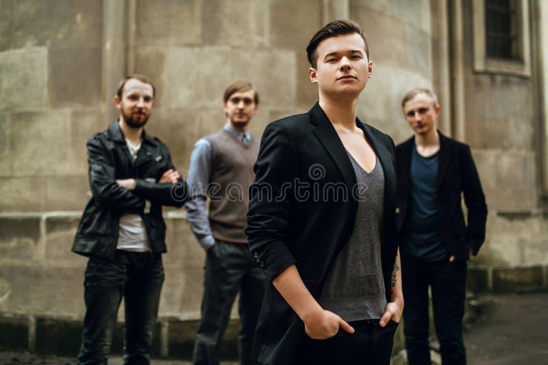 Stilfull stilig grupp av män som står och poserar på backgroen royaltyfri foto