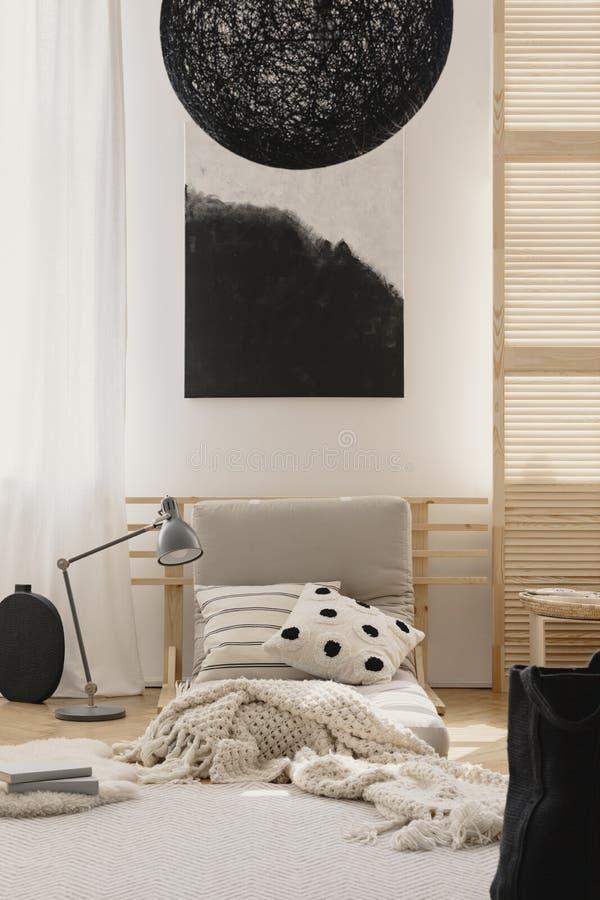 Stilfull svart ljuskrona och svartvit abstrakt målning i japanskt inspirerat beige sovrum royaltyfri bild