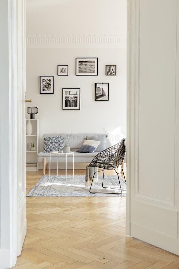 Stilfull svart metallstol i flott vit vardagsrum som ?r inre med hyreshusen royaltyfri fotografi