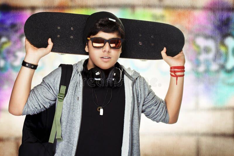 Stilfull tonårig pojke med skateboarden arkivbild